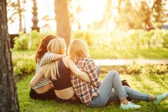 Opinião traseira três mulheres bonitas que sentam-se na grama e nos abraços Fotografia de Stock