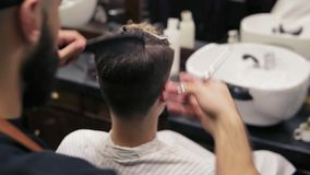 Opinião traseira um cliente que senta-se pelo espelho quando um barbeiro farpado executar um corte de cabelo com as tesouras e pe video estoque