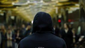 Opinião traseira um homem com um escuro - hoodie azul em estar na frente de uma multidão na estação, conceito da resistência Fim  filme