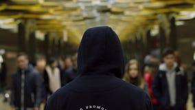 Opinião traseira um homem com um escuro - hoodie azul em estar na frente de uma multidão na estação, conceito da resistência Fim  vídeos de arquivo