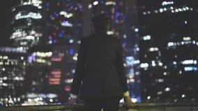 Opinião traseira um homem de negócios em uma cidade grande na noite Imagem de Stock