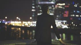 Opinião traseira um homem de negócios em uma cidade grande na noite Fotografia de Stock Royalty Free