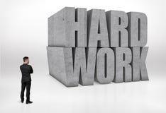 A opinião traseira um homem de negócios que olha o concreto grande 3D exprime 'o trabalho duro', isolado no fundo branco Imagens de Stock Royalty Free