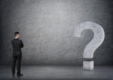 Opinião traseira um homem de negócios que olha o ponto de interrogação grande do concreto 3D Imagem de Stock Royalty Free