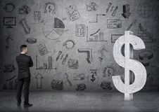 Opinião traseira um homem de negócios que olha o sinal de dólar 3D concreto grande Fotos de Stock