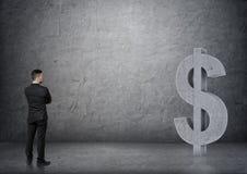Opinião traseira um homem de negócios que olha o sinal de dólar 3D concreto grande Fotografia de Stock Royalty Free