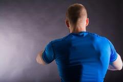 Opinião traseira um homem novo muscular que está no estúdio no fundo escuro Fotografia de Stock