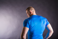 Opinião traseira um homem novo muscular que está no estúdio no fundo escuro Imagens de Stock Royalty Free
