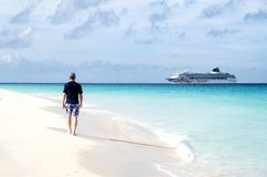 Opinião traseira um homem que anda em uma praia das caraíbas e que olha um navio de cruzeiros fotos de stock royalty free