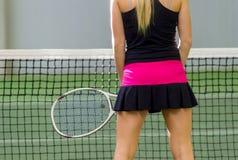 Opinião traseira um jogador de tênis fêmea com uma raquete na ação fotografia de stock royalty free
