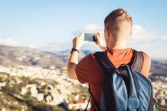 Opinião traseira um turista do homem novo com a trouxa que toma a foto da paisagem com smartphone fotos de stock royalty free