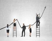 Opinião traseira uma equipe do negócio que tira um grande gráfico crescente preto em um muro de cimento Fotos de Stock