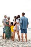 Opinião traseira uma família feliz que levanta na praia fotos de stock