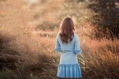 Opinião traseira uma jovem mulher ou uma menina bonita muito no prado do verde que olham o por do sol imagem de stock