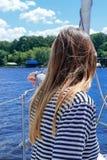 Opinião traseira uma jovem mulher que aprecia a navigação em um iate fotografia de stock royalty free