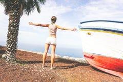 Opinião traseira uma jovem mulher que levanta suas mãos acima ao admirar a vista panorâmica do oceano do monte fotos de stock