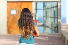 Opinião traseira uma menina adolescente que anda para a escola imagens de stock