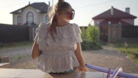Opinião traseira uma menina consideravelmente bonito nos fones de ouvido que lê o livro, o plano pequeno que encontra-se no patam filme
