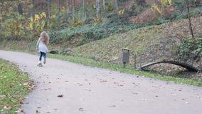 Opinião traseira uma menina que skateboarding no trajeto perto da floresta filme