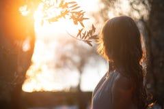 Opinião traseira uma mulher bonita nova no por do sol e vista ao horizonte de mar imagem de stock