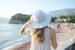 Opinião traseira uma mulher bonita nova que guarda seu chapéu de palha na praia e que olha ao horizonte de mar foto de stock