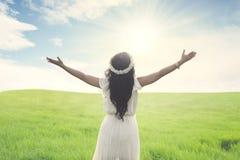 A opinião traseira uma mulher com o cabelo longo que está com os braços largos abre no campo verde foto de stock