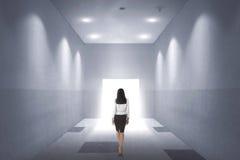 Opinião traseira uma mulher de negócio asiática nova que anda à porta aberta Imagem de Stock Royalty Free