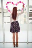 Opinião traseira uma mulher do moderno que faz um coração no post-it Imagem de Stock Royalty Free