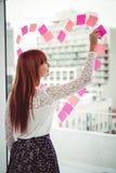 Opinião traseira uma mulher do moderno que faz um coração no post-it Imagens de Stock Royalty Free