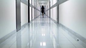 Opinião traseira uma mulher em um vestido preto que anda ao longo do corredor do hotel Está guardando sapatas em sua mão video estoque