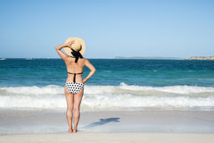 Opinião traseira uma mulher na polca Dot Bikini Standing em uma praia 2 fotos de stock royalty free
