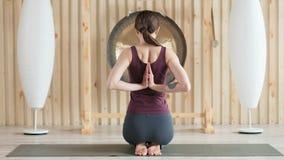 Opinião traseira uma mulher nova da ioga que estica as mãos ao sentar-se no assoalho video estoque