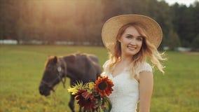 Opinião traseira uma noiva nova que está perto de um cavalo Girando ao redor, sorriso, olhando para baixo Movimento lento video estoque
