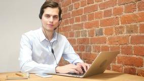 Opinião um homem atrativo novo que trabalha no portátil que mostra os polegares acima, centro de atendimento vídeos de arquivo