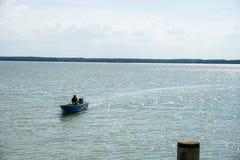 Opinião um homem que dirige um barco através de um rio calmo fotografia de stock royalty free