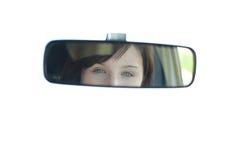 Opinião uma mulher nova através do espelho rear-view Fotografia de Stock Royalty Free