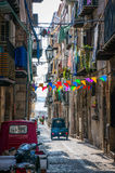 Opinião velha da rua do estreito da cidade de Cefalu com os carros estacionados e os balcões pequenos na manhã imagens de stock