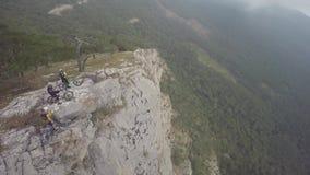 Opinión aérea épica los motoristas de la montaña que se colocan en la montaña en la niebla Cielo nublado, estación del otoño metrajes