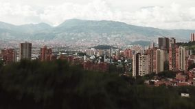 Opinión aérea ascendente del abejón que muestra la ciudad de Colombia Medellin detrás de un árbol almacen de metraje de vídeo