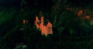 Opinión aérea asombrosa del castillo de Neuschwanstein, cielo de oro, crepúsculo de la puesta del sol en las montañas bávaras, Ba almacen de metraje de vídeo