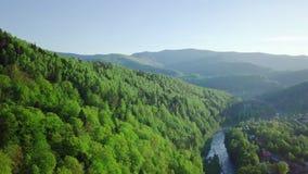 Opinión aérea de la cantidad del abejón: Vuelo sobre pueblo de montaña de la primavera con el bosque en luz suave de la salida de metrajes
