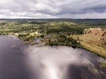 Opinión aérea de la naturaleza del contryside de Ontario Canadá que mira abajo desde arriba del río que fluye dentro del lago Foto de archivo libre de regalías