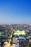 Opinión aérea de la noche de la ciudad del horizonte del ojo moderno panorámico del pájaro bajo resplandor de neón dramático y ci Fotografía de archivo libre de regalías