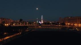 Opinión aérea de la noche de la noria y del puente encendidos contra el cielo con la luna, Valencia, España almacen de metraje de vídeo