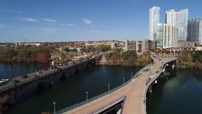 Opinión aérea de levantamiento delantera lenta el horizonte de Austin y el puente peatonal y los kayakers de Pfluger almacen de metraje de vídeo