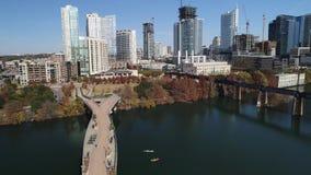 Opinión aérea de levantamiento lenta el horizonte de Austin y el puente peatonal y los kayakers de Pfluger almacen de metraje de vídeo