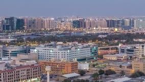 Opinión aérea de los edificios del canal moderno y viejo de Deira del día de Dubai Creek al timelapse de la noche almacen de metraje de vídeo