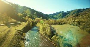 Opinión aérea de UHD 4K Vuelo bajo sobre el río, el prado y el camino fríos frescos de la montaña en la mañana soleada del verano almacen de video