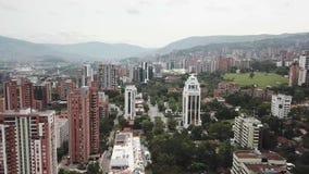 Opinión aérea del abejón al revés que vuela de la ciudad de Medellin en Colombia que muestra tráfico y de los edificios rodeados  almacen de metraje de vídeo