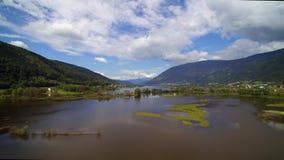 Opinión aérea del abejón del camino austríaco Ossiach de la ciudad de las montañas del mar y del bosque de Ossiacher del lago almacen de video